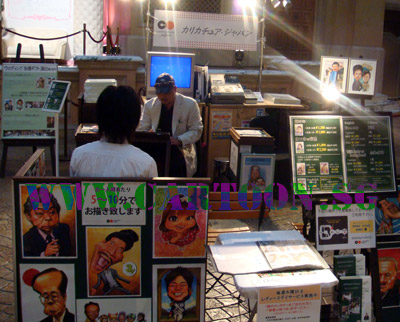 Singapore caricature artist drawing caricatures at a stand in Tokyo, Japan