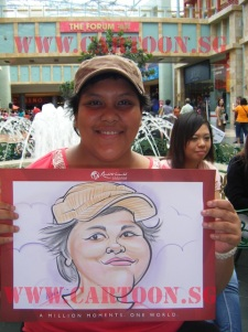 Lady showing off caricature done by Cartoon.sg