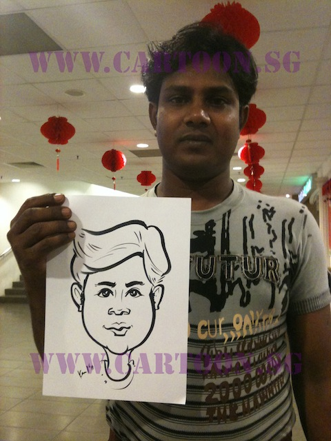 Indian guy posing with his caricature at NTU almni